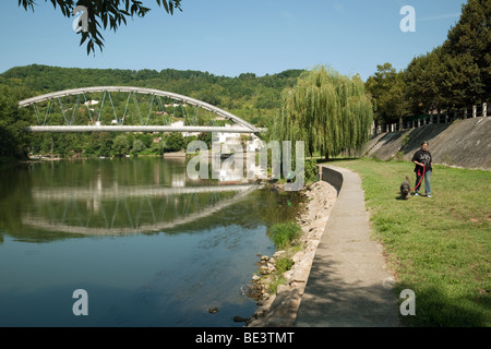 A woman walking her dog with, in the background, the bridge across the river Lot at Castelmoron sur Lot, Aquitaine, - Stock Photo