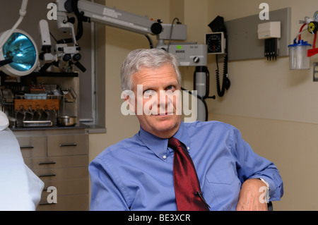 Ear nose and throat doctor or otolaryngologist in the clinic examining room - Stock Photo