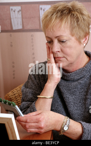Grieved senior woman holding a photo frame and looking at the picture in her hand. - Stock Photo