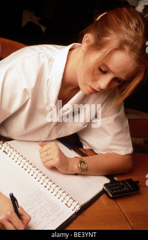 Young district nurse writing up her notes during visit - Stock Photo