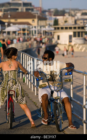 A couple riding dragster bicycles along the Promenade at Bondi Beach. Sydney, New South Wales, AUSTRALIA - Stock Photo