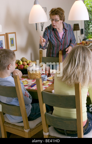 Verbal abuse: Demanding mother telling off her children at home at dining table and being an aggressive mom. SerieCVS417009 - Stock Photo