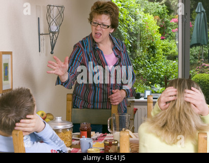 Stressed mother disciplining her frightened children at breakfast table - SerieCVS417009 - Stock Photo