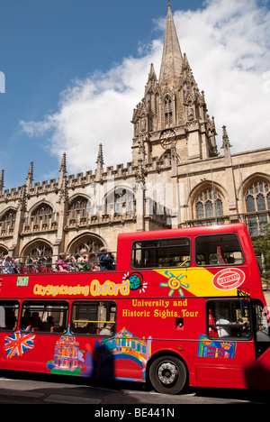 Tour bus passing The University Church of Saint Mary The Virgin on Oxford's High Street - Stock Photo