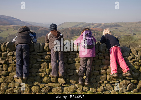 Four children taking a break from their walk, perching and leaning on a dry stone wall, admiring the view over Wharfedale. - Stock Photo