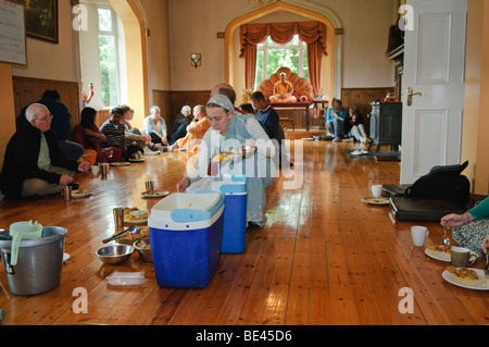 Disciples and visitors eating a vegetarian feast at a Hare Krishna temple room