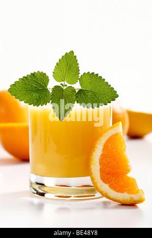 Glass of orange juice with mint and orange slice - Stock Photo