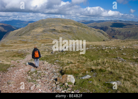 Lone woman walking on the Cumbrian Fells, Lake District - Stock Photo