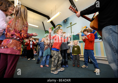 CHILDREN SINGING AND DANCING IN A GROUP AT A SUNDAY SCHOOL UK - Stock Photo