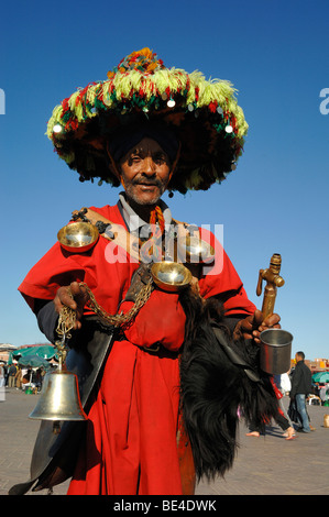 Moroccan Water Seller in Traditional Costume with Pewter Cups & Bell in Djemaa El-Fna or Djemaa El Fna Square Marrakesh - Stock Photo