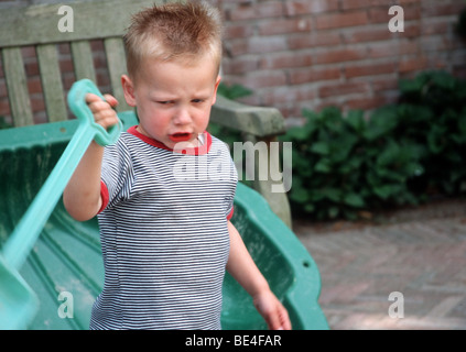 Defiant young boy showing aggressive unwanted behavior. - Stock Photo