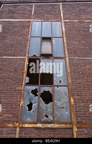 Broken windows in the facade, factory building on factory premises of the former Deutsche Norton GmbH, manufacturer - Stock Photo