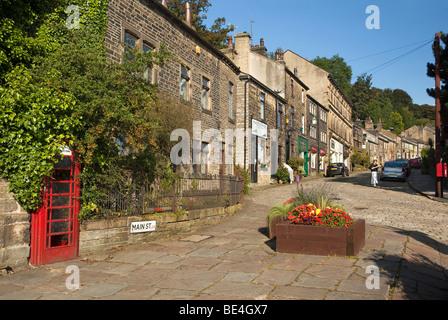 UK, England, Yorkshire, Haworth, Main Street, overgrown K6 phone box built into wall - Stock Photo
