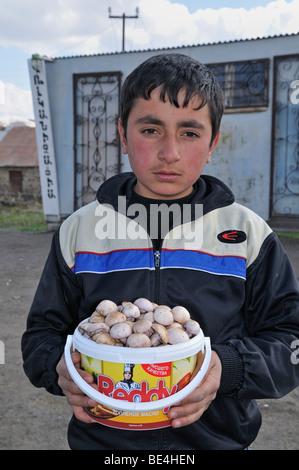 Armenian boy selling mushrooms in a poor mountain village near Sisian, Armenia, Asia