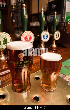 UK, England, Yorkshire, Haworth, Fleece Inn pint and half of locally brewed Timothy Taylors beer on bar - Stock Photo
