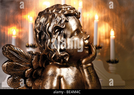 Golden Christmas angel in front of candleholder for windowsill, window pyramid - Stock Photo