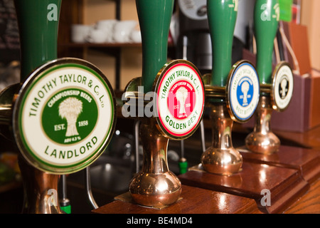 UK, England, Yorkshire, Haworth, Timothy Taylor's Keighley Brewery beer hand pumps on bar - Stock Photo