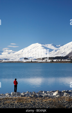 Woman by Lake Tekapo and Two Thumb Range in Winter, Mackenzie Country, Canterbury, South Island, New Zealand - Stock Photo