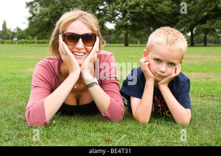 Horizontal close up portrait of a young boy and his mum lying together with their head in their hands on the grass - Stock Photo
