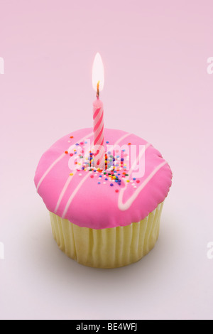 Pink candle in cup cake for first birthday - Stock Photo
