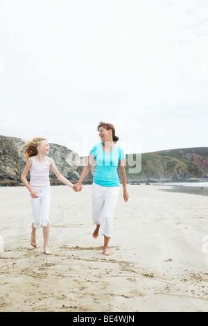 Woman running along the beach, hand in hand with a girl - Stock Photo