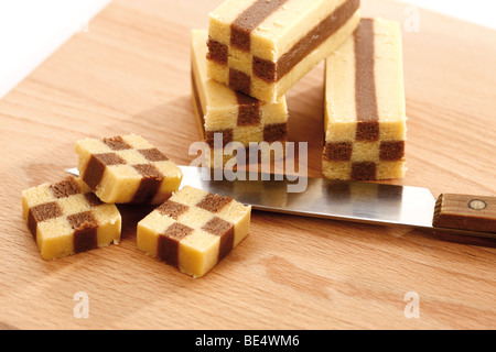 Black and white cookies, checkerboard bars on wooden board with knife - Stock Photo