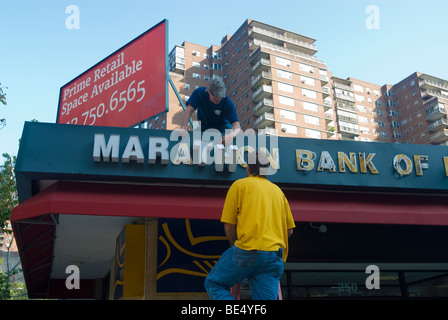 Workers remove the letters from the sign for the Marathon Bank of New York's branch in the Chelsea neighborhood - Stock Photo