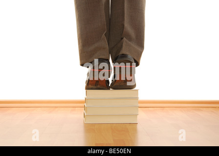 Manager standing on a pile of books, symbolic image for knowledge is power - Stock Photo