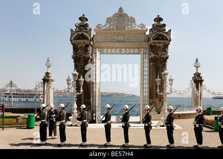 Guard at the main gate in front of the Bosphorus shore, Dolmabahce Palace, Besiktas, Istanbul, Turkey - Stock Photo