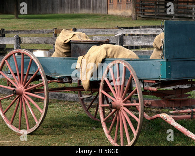 Old wooden horse drawn wagon used on a farm for transporting supplies. There are burlap bags on the wagon. - Stock Photo