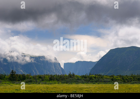 Clouds over steep cliffs of Western Brook Pond in Gros Morne National Park Newfoundland Canada - Stock Photo