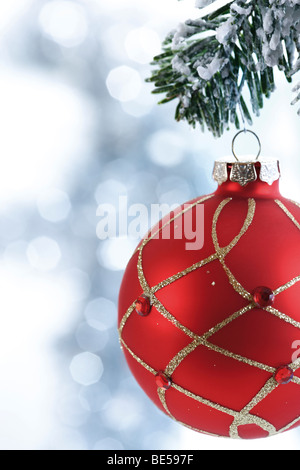Red Christmas ball with decoration on fir branch - Stock Photo