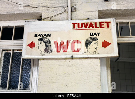 Toilet sign with naively painted heads of men and women, book bazaar, Beyazit Square, Istanbul, Turkey - Stock Photo