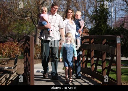 Family walking across bridge at park - Stock Photo
