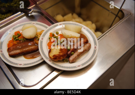 School dinners - sausage vegetables and potatoes -  served up on plates in a primary school canteen hall, Wales - Stock Photo