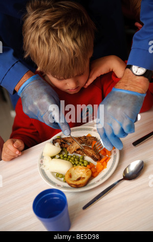 Adult wearing blue latex gloves cutting the food up for a young child during school dinner in a primary school, - Stock Photo