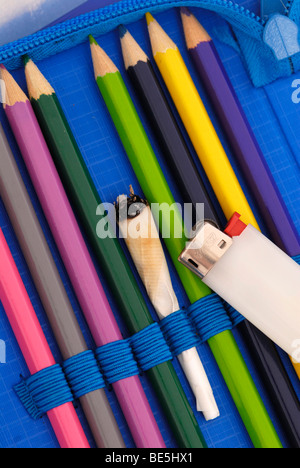 Joint in a pencil case, symbolic image for drug use among adolescents - Stock Photo