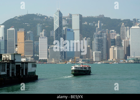 Star Ferry departing from Kowloon in front of the skyline of Central Hong Kong, Financial District, Hong Kong, China, - Stock Photo