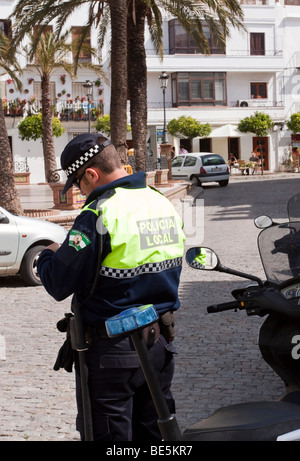 Spanish policeman of the Policia Local is writing parking tickets, Vejer de la Frontera, Andalusia, Spain, Europe - Stock Photo