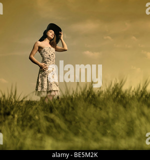 Young woman with a flowery summer dress and large hat is standing in a meadow and looking into the sun - Stock Photo
