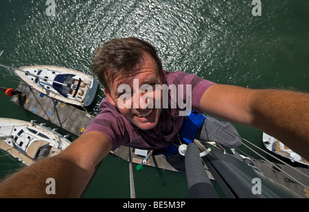 Neil Foster at the top of a Southerly 35 mast. - Stock Photo