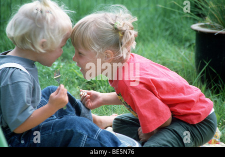 Cute siblings playing in the garden - Stock Photo