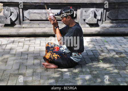 Young man bringing offerings to the gods, Denpasar, Bali, Indonesia, Southeast Asia - Stock Photo