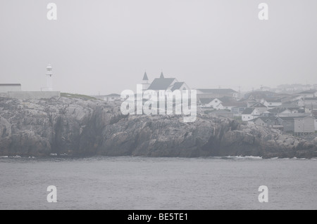 Channel Port aux Basques Newfoundland lighthouse and Anglican church from the coast in fog Cabot Strait Atlantic - Stock Photo