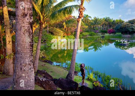 Pond and garden sculpture at Na Aina Kai Botanical Gardens. Kauai, Hawaii - Stock Photo