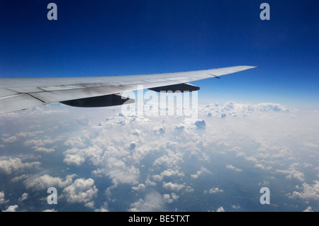 Plane wing above white cumulus clouds - Stock Photo