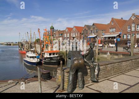 Shrimp boats in the harbor of Neuharlingersiel, in front the bronze sculpture Altfischer und Jungfischer, Old Fisherman - Stock Photo