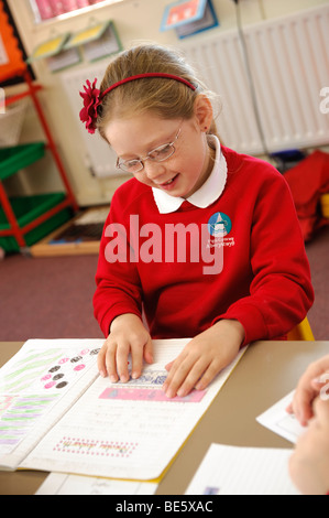 Young child reading from her exercise course book in a Welsh language medium primary school, Wales UK - Stock Photo