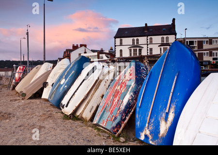 Early morning in Rhos harbour with the rowing boats stood up and tied to the harbour wall in Rhos on Sea, Colwyn - Stock Photo