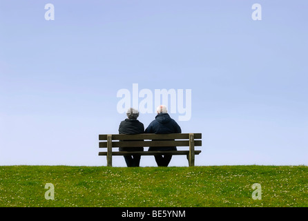 Elderly couple sitting on a bench on a dike - Stock Photo